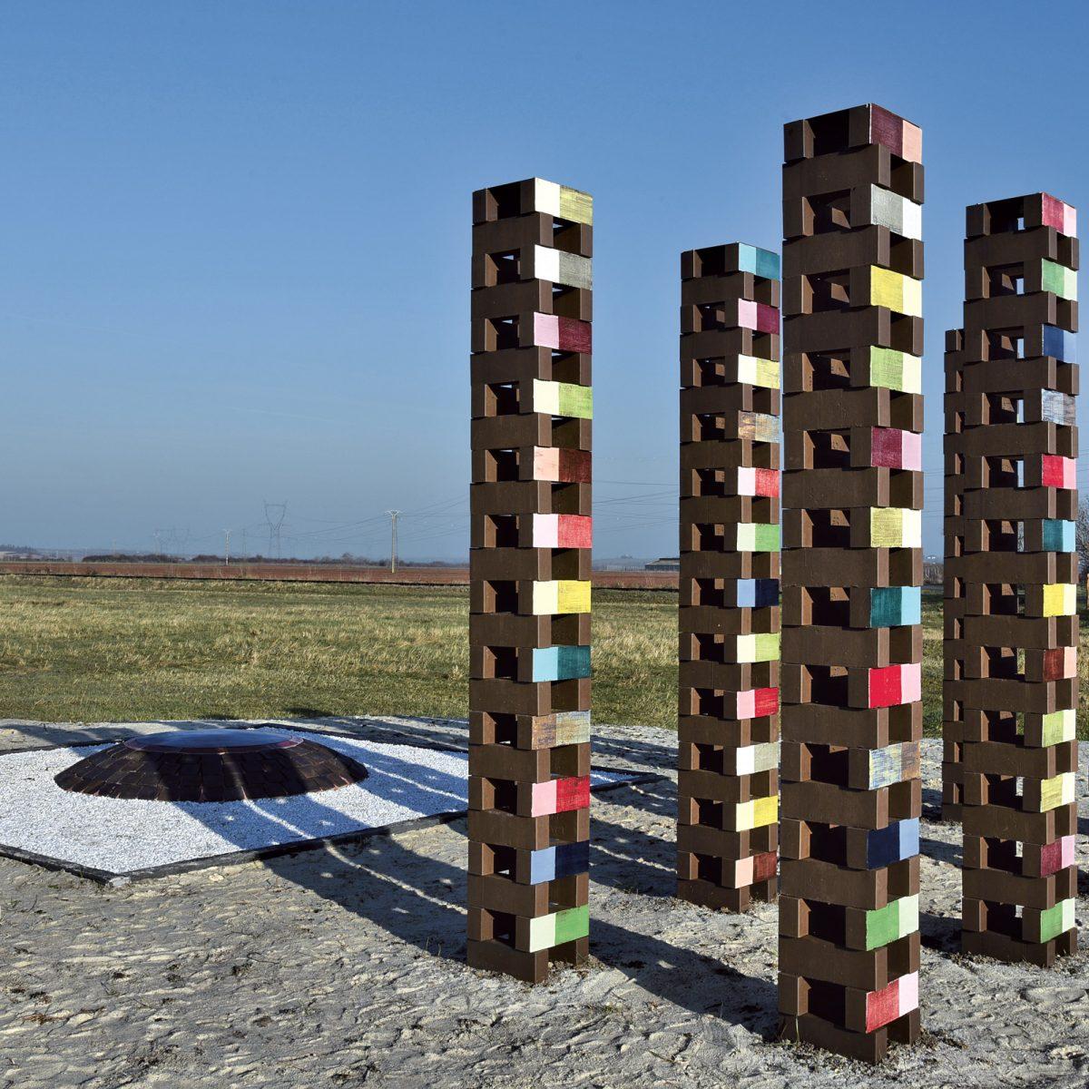 8 colonnes ajourées en briques couleur réglisse dont une face est émaillée de plusieurs couleurs vives et pétillantes.